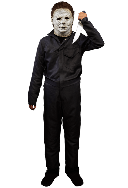 This is a boy standing wearing a Michael Myers Halloween 2018 movie costume of grey coveralls, wearing a white mask with brown hair and holding a knife.