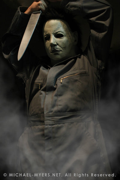 This is a Halloween 6 Curse of Michael Myers mask that is white with brown hair and black eyes and he is wearing coveralls and holding a knife above his head.