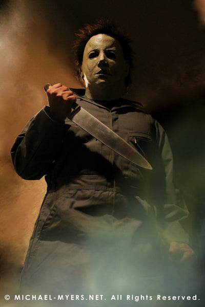 This is a Halloween 6 Curse of Michael Myers mask that is white with brown hair and black eyes and he is wearing coveralls and standing in fire and holding a knife..