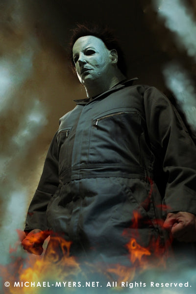 This is a Halloween 6 Curse of Michael Myers mask that is white with brown hair and black eyes and he is wearing coveralls and standing in fire.