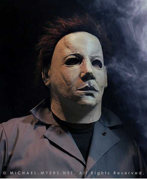 This is a Halloween 6 Curse of Michael Myers mask that is white with brown hair and black eyes and he is wearing coveralls.