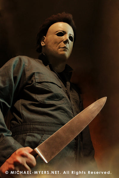 This is a Michael Myers Halloween H20 Mask that is white with brown hair and he is wearing green coveralls and holding a knife in his hand.