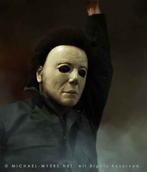 This is a Michael Myers Halloween H20 Mask that is white with brown hair and he is wearing green coveralls, while standing in smoke..