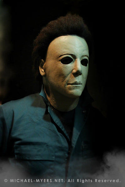 This is a Michael Myers Halloween H20 Mask that is white with brown hair and he is wearing green coveralls.