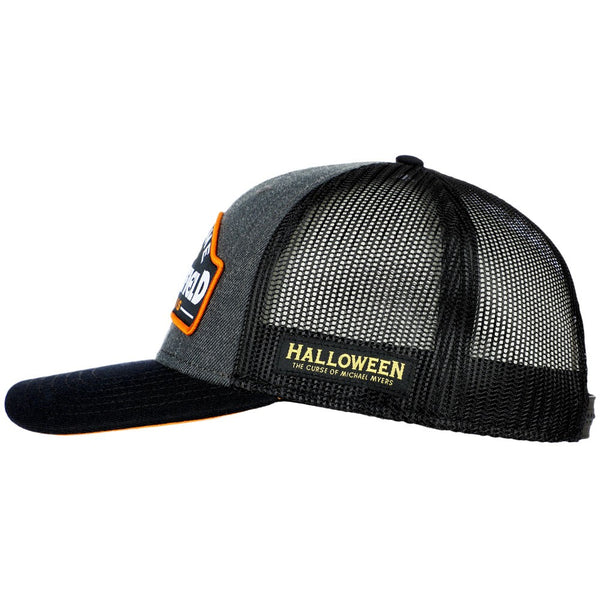 This is a grey Halloween movie Haddonfield Michael Myers trucker hat with black mesh and a tag that says Curse of Michael Myers.