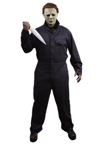 This is a man standing wearing a Michael Myers Halloween 2018 movie costume of grey coveralls, wearing a white mask with brown hair and holding a knife.