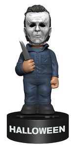 This is a 2018 Halloween Michael Myers Body Knocker from NECA and he has a grey coverall, a grey weathered mask with brown hair and is holding a silver knife.