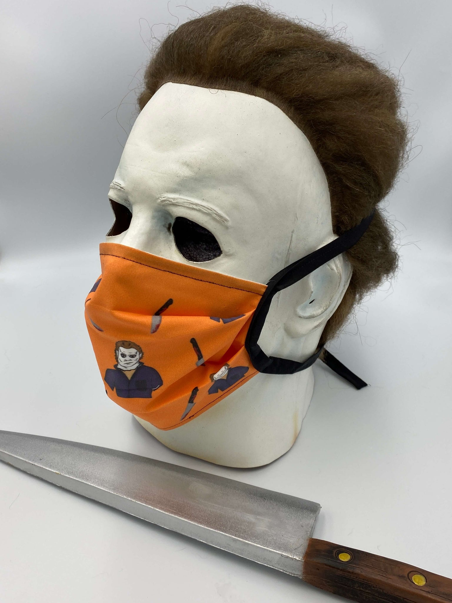 This is a Halloween Michael Myers protective cotton face mask and it is orange, he has a white mask and there is a bloody knife.