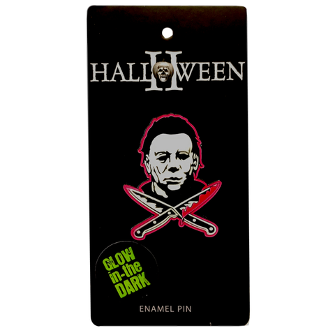 This is a Halloween Michael Myers enamel pin and he has a white mask and there are two bloody knives in front of him.