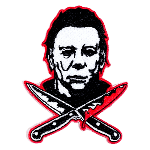 This is a Halloween Michael Myers patch that has a white face, dark hair and two bloody knives, that are crossed.