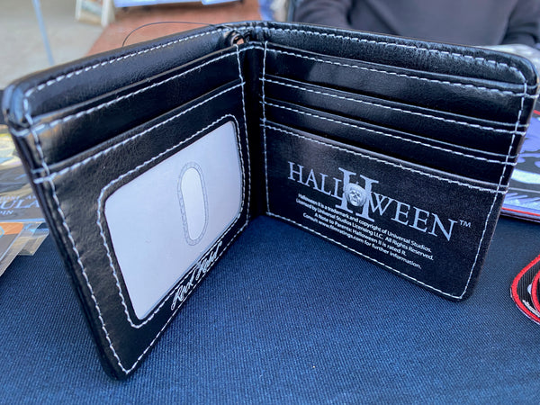 This is the inside of a Halloween Michael Myers wallet that is black and has slots for cards and a clear plastic license holder.