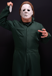 This is a Halloween 2 Michael Myers coverall that is green with pockets and he is wearing a white mask with brown hair and holding a knife.
