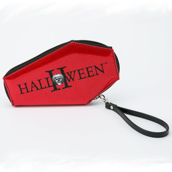This is a Halloween Michael Myers coffin shaped wallet and it has red glitter, a pumpkin and a black wrist strap.