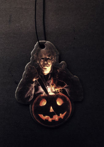 This is a Halloween movie Michael Myers air freshener and he has a white face, is holding a knife and an orange pumpkin that has a smile face.