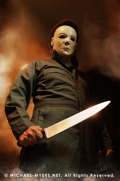 This is a Halloween 8 Resurrection Michael Myers mask that is a white face, brown hair and black eyes with coveralls, a silver and shiny knife, with fire.