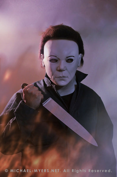 This is a Halloween 8 Resurrection Michael Myers mask that is a white face, brown hair and black eyes with coveralls, a silver and shiny knife, with white smoke and fire.