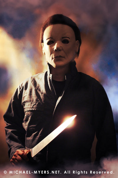 This is a Halloween 8 Resurrection Michael Myers mask that is a white face, brown hair and black eyes with coveralls, a silver and shiny knife and white smoke.