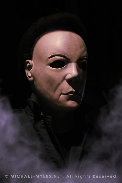 This is a Halloween 8 Resurrection Michael Myers mask that is a white face, brown hair and black eyes with coveralls and white smoke.
