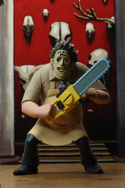 This Toony Terrors Leatherface is posing with a chainsaw in front of a red wall that has animal skulls on it.