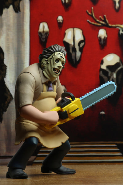 Leatherface is standing to the side with a chainsaw in front of a red wall that has animal skulls on it.