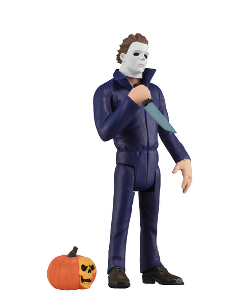 Michael Myers action figure is standing to the side with a knife in his hand, with a pumpkin at his feet, in front of a white background.