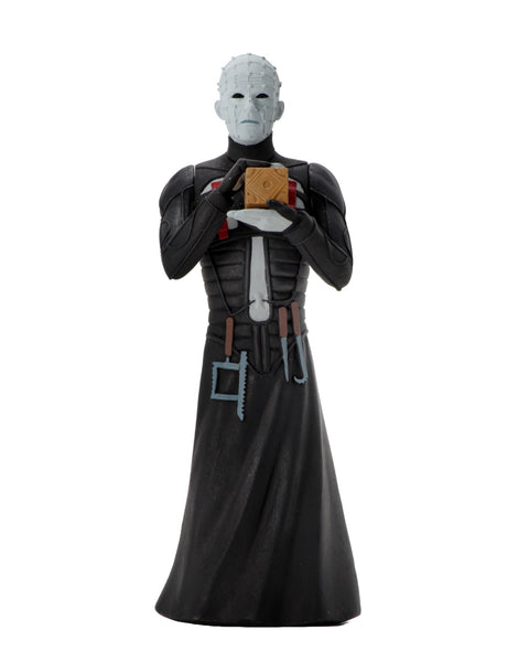 A pinhead man action figure in a black leather dress, with tools hanging, who is holding a brown box.