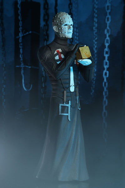 A pinhead man in a black leather dress, with tools hanging, who is holding a brown box, while surrounded by blue light and chains hanging from the wall.