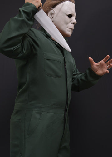This is a Halloween II Michael Myers coveralls that are green with pockets and he is wearing a white mask with brown hair and holding a knife.
