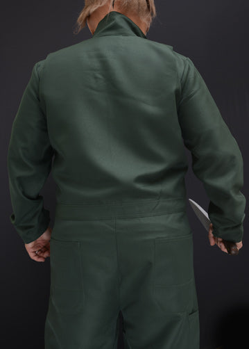 This is a Halloween II Michael Myers coveralls that are green with pockets and he is wearing a mask with brown hair and holding a knife