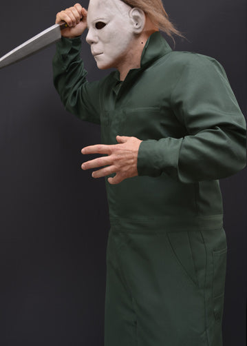 This is a Halloween II Michael Myers coveralls that are green with pockets and he is wearing a white mask with brown hair and holding a knife