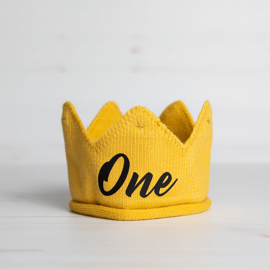 Knitted gold crown with One in black lettering and gold accents