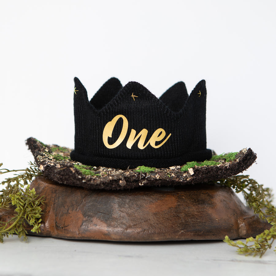 Black knitted crown with One in gold lettering and gold accents