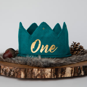 Teal knitted crown with One in gold lettering and gold accents