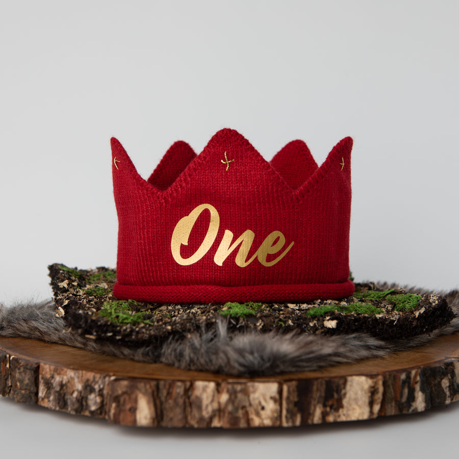 Red knitted crown with One in gold lettering and gold accents