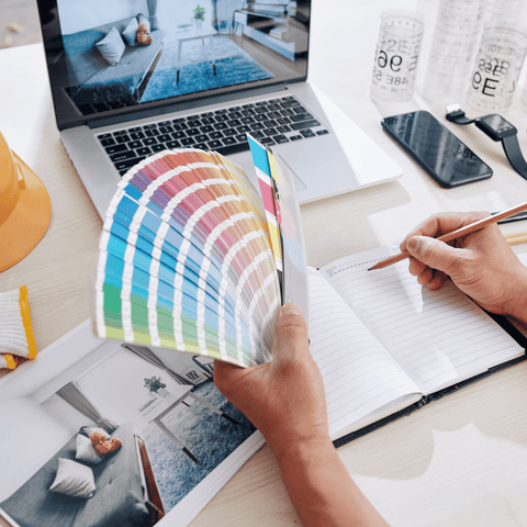 Designer working on color scheme for living room of client and writing ideas in planner