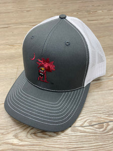 Cocky leaning on tree trucker hat