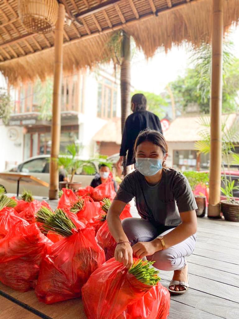 Balinese woman packing food parcels