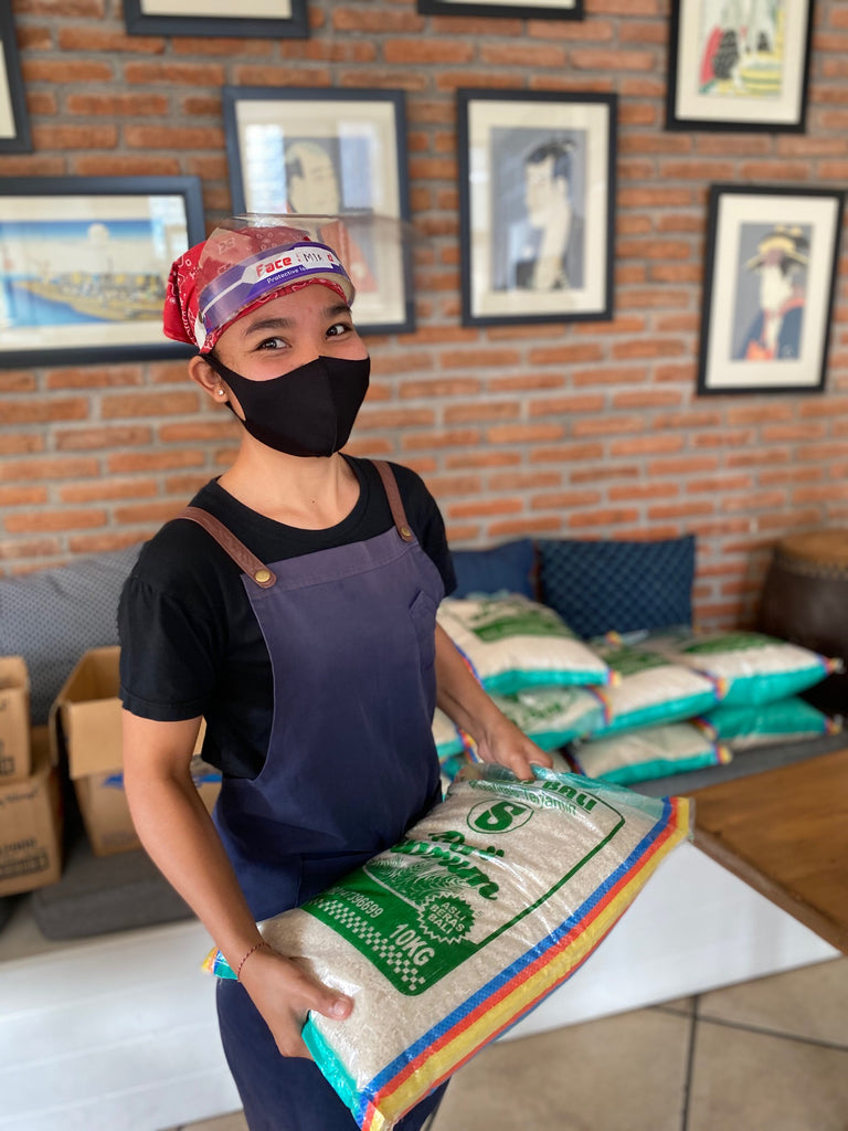 Woman in mask holding rice