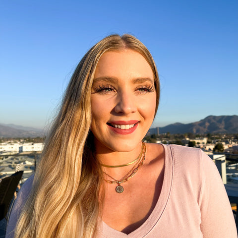 blonde white women wearing a gold herringbone choker, a gold coin necklace, and a gold paperclip necklace layered. She's looking at the camera and smiling wearing a pink shirt during golden hour.