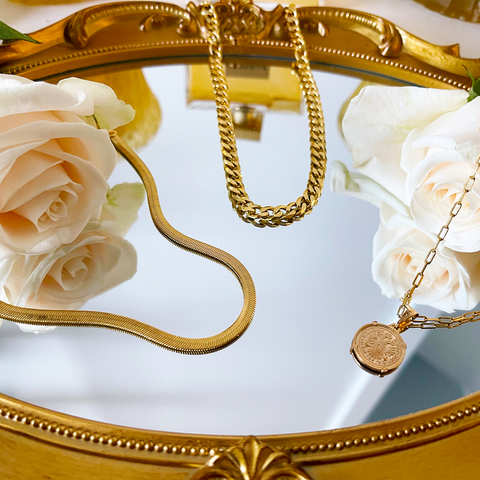 mgold irror laying face up with two roses on it and a gold herringbone choker, gold curb chain, and a coin necklace