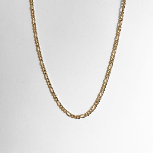 gold figaro link chain on gray background