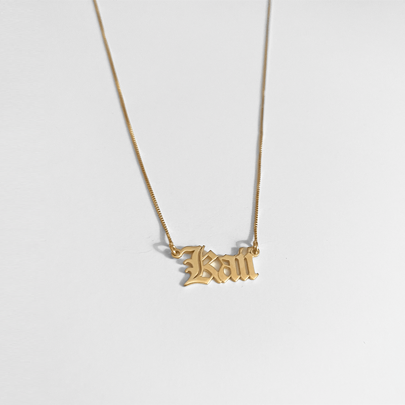 gold name necklace on gray background