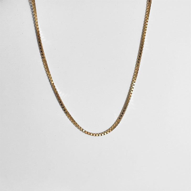 gold chain box necklace on gray background