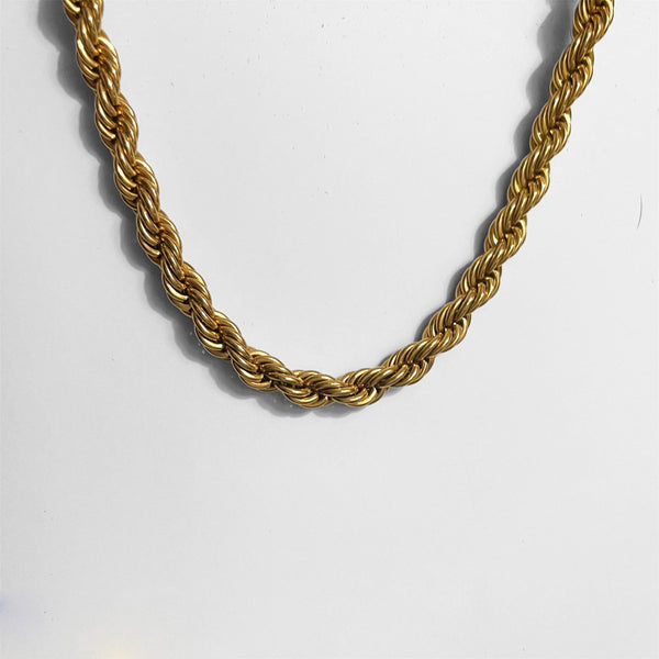 gold rope necklace on gray background