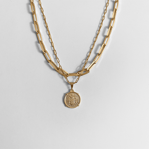 Gold coin pendant necklace & paperclip necklace on gray background
