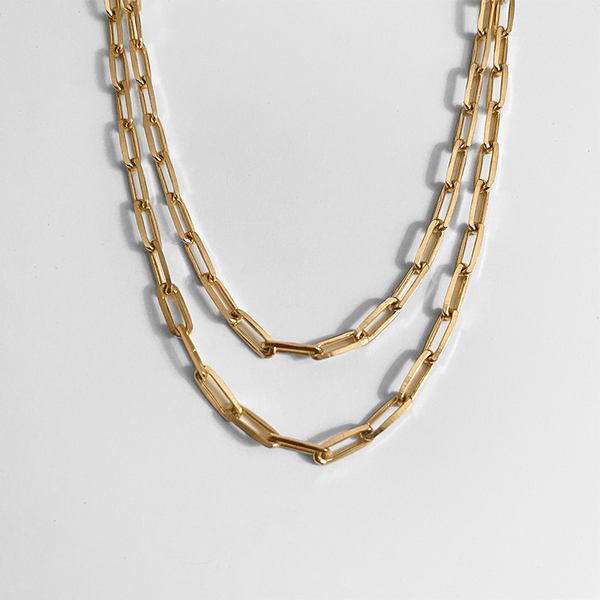 two gold paperclip chain necklace on gray background