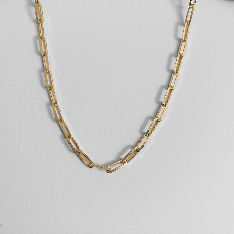 paper clip chain in gold on gray background