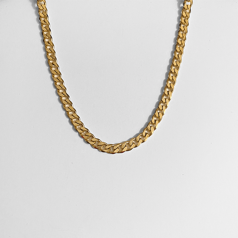 gold curb chain necklace on gray background