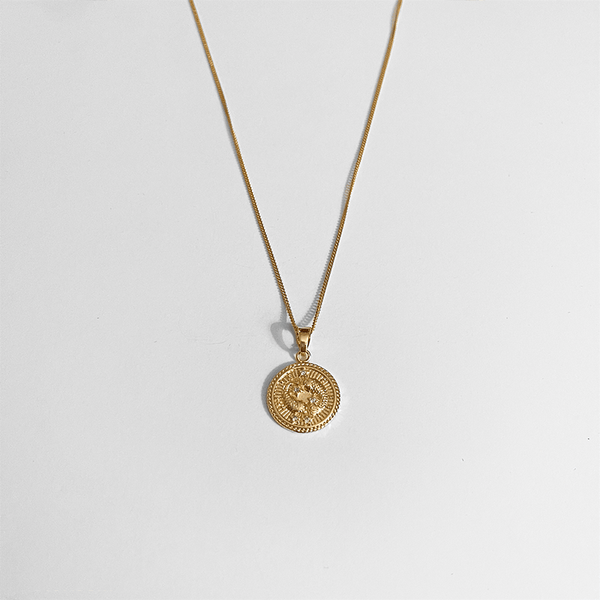 zodiac necklace gold on gray background