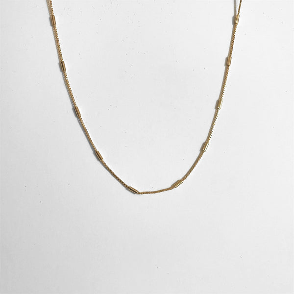 skinny gold box chain on gray background